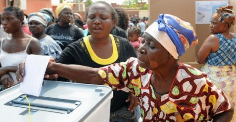 An Angolan (R) is helped to cast her ballot at a polling station.  By Francisco Leong (AFP/File)