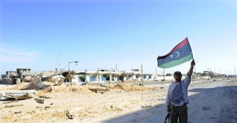 A Libyan National Transitional Council (NTC) fighter waves his new national flag in Sirte.  By Philippe Desmazes (AFP)