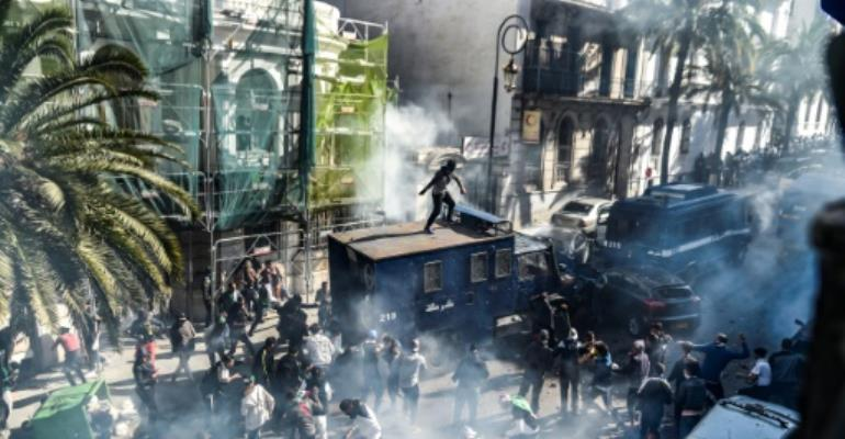 Clashes erupt between Algerian protesters and riot police during a  demonstration in Algiers, the eighth Friday in a row that protestors have taken to the streets.  By RYAD KRAMDI (AFP)