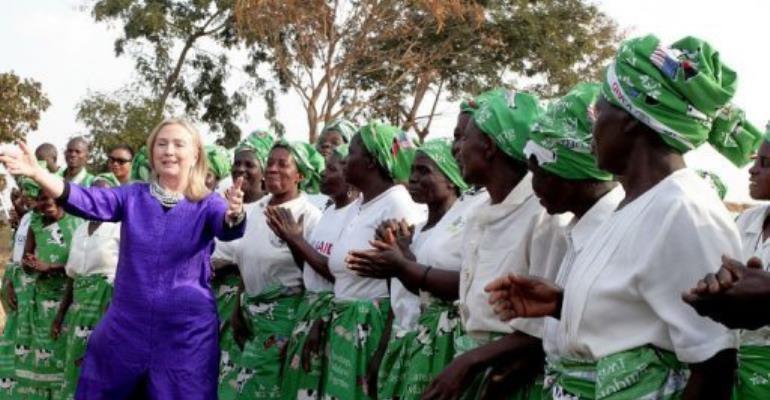 US Secretary of State Hillary Clinton (L) dances with Malawian women.  By Amos Gumulira (AFP)