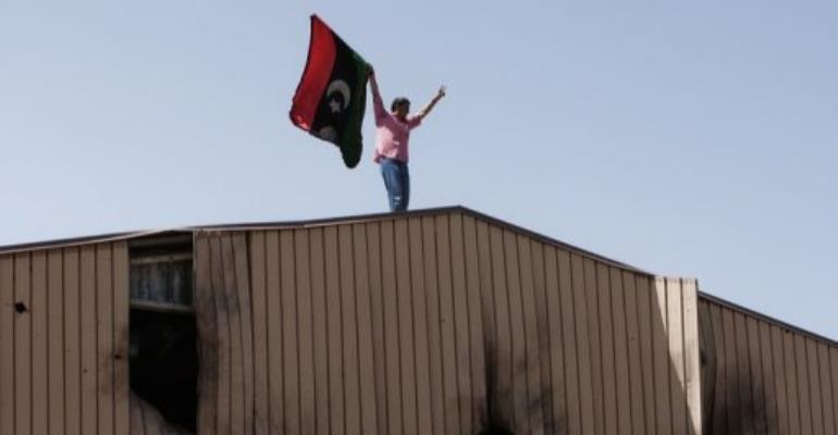 A man waves a Libyan rebel flag on top of bullet riddled warehouse in Benghazi today.  By - (AFP)