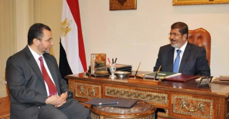 Egyptian President  Mohamed Morsi (right) meets with newly appointed Prime Minister Hisham Qandil in Cairo on July 24.  By  (AFP/Egyptian Presidency/File)