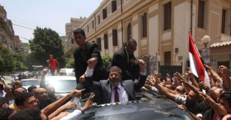 Egyptian Muslim Brotherhood candidate Mohammed Mursi (C) waves to his supporters as he leaves a polling station.  By  (AFP)