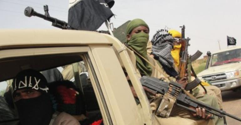 Figthers of the Islamic group Ansar Dine stand guard at Kidal airport, northern Mali on August 7, 2012.  By Romaric Hien (AFP/File)