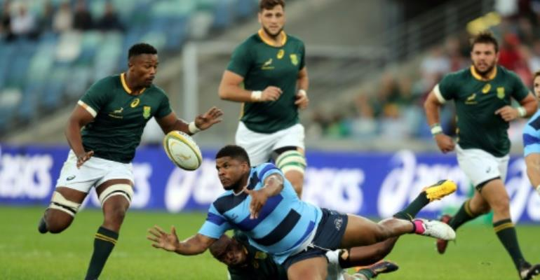 France's Barbarians Jonathan Danty (C) is tackled by South Africa's Lwazi Mvovo during test match between Barbarians and South Africa on June 16, 2017 in Durban, South Africa.  By ANESH DEBIKY (AFP)