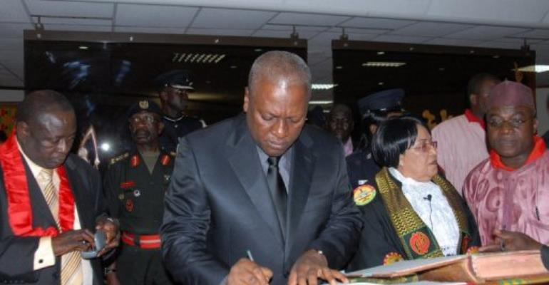 Ghana's Vice President John Dramani Mahama (C) signs documents after taking the oath of office as head of state.  By Adadevoh David (AFP)