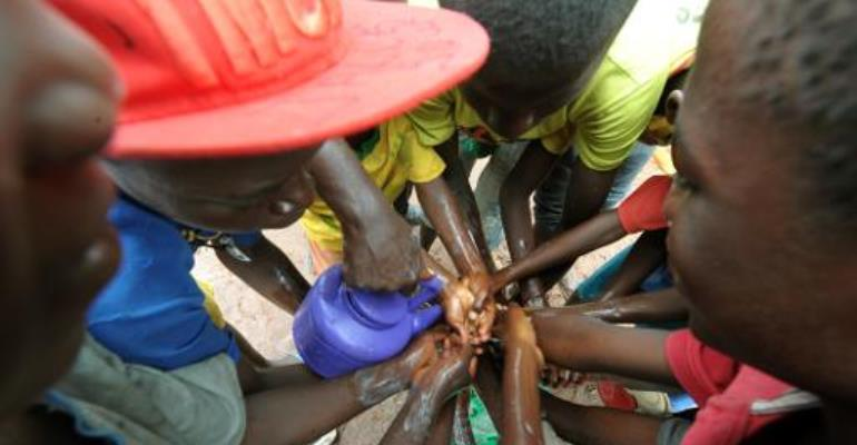People wash their hands with soap and bleach on September 3, 2014 to prevent the spread of the Ebola virus in the northern Senegalese city of Diaobe.  By Seyllou (AFP)