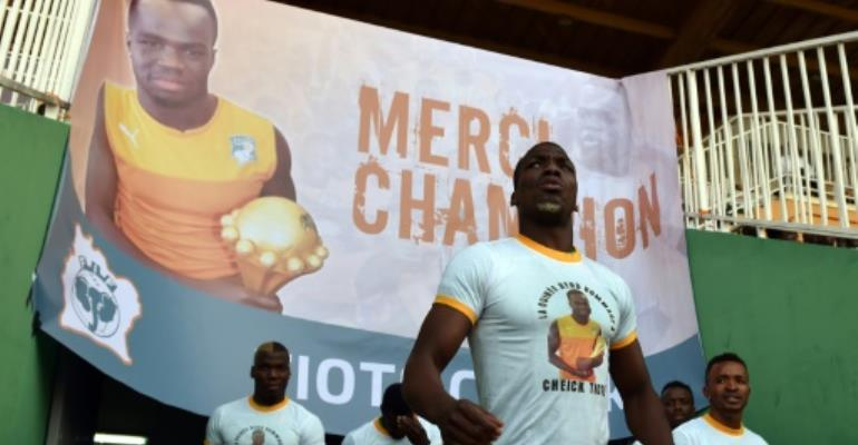 Guinea's players wearing tee-shirts with a picture of Cheick Tiote enter the stadium under a poster reading,