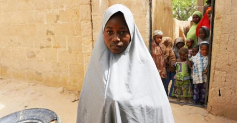 Hassana Mohammed, 13, who scaled a fence to escape an alleged Boko Haram attack on her Government Girls Science and Technical College, stands outside her home in Dapchi, Nigeria, on February 22, 2018.  By AMINU ABUBAKAR (AFP/File)