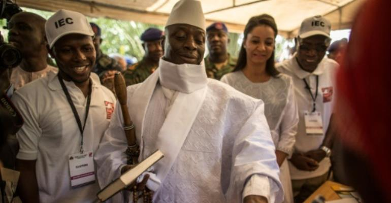 Incumbent Gambian president Yahya Jammeh (C) has his finger inked before casting his marble in a polling station in a presidential poll, in Banjul on December 01, 2016.  By MARCO LONGARI (AFP/File)