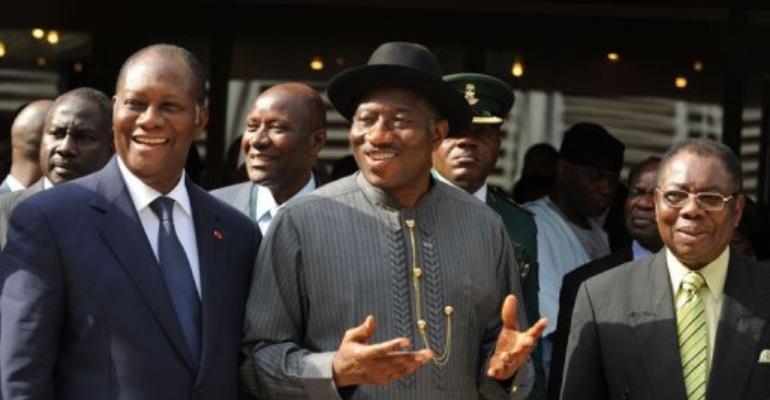 Outgoing chairman Nigerian President Goodluck Jonathan (C) passes the torch to Ivorian President Alassane Ouattara (L).  By Pius Utomi Ekpei (AFP)