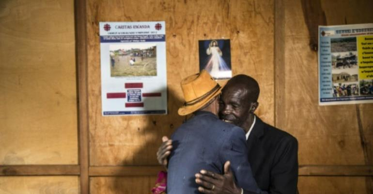 Jean-Bosco Gakwenzire, 65, of Tutsi ethnicity, embraces his old school mate Pascal Shyirahwamaboko (R), 68 with his wife Rose (hidden), both Hutu.  By JACQUES NKINZINGABO (AFP)