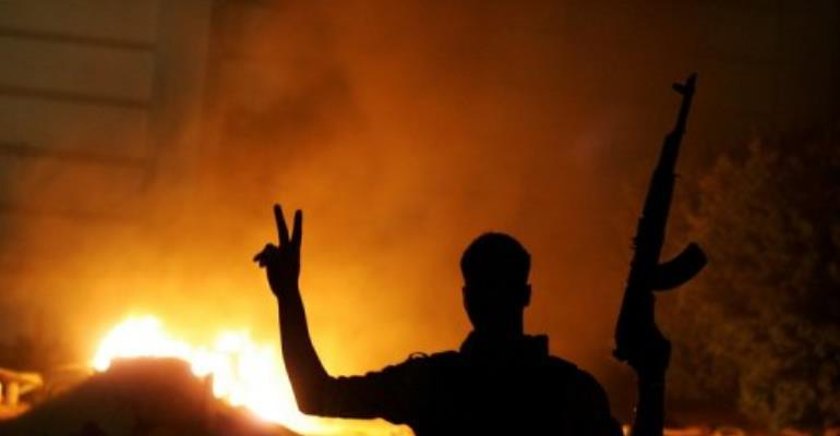 An armed libyan man flashes the victory sign in front of the Ansar el-Sharia headquarters in Benghazi.  By Abdullah Doma (AFP/File)