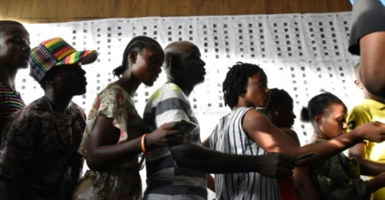 Liberians wait outside a polling station to vote in Monrovia.  By ISSOUF SANOGO (AFP)