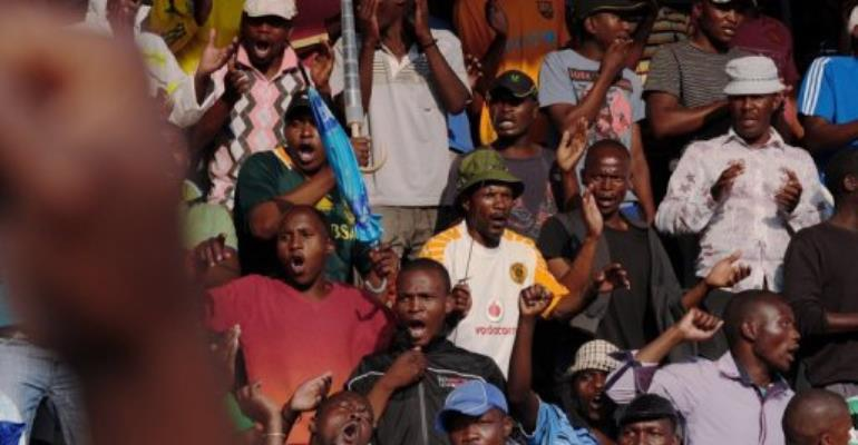 Striking miners gesture as they celebrate having secured a 22 percent pay hike from Lonmin platinum mine on September 18.  By Alexander Joe (AFP/File)