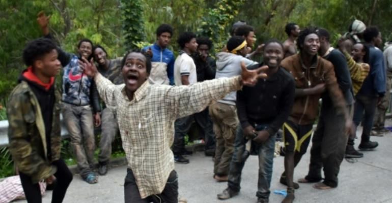 Migrants celebrate after forcing their way through a fence between Morocco and the tiny Spanish enclave of Ceuta, on February 17, 2017.  By Antonio SEMPERE (AFP)