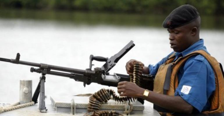 A naval officer assembles his machine gun before starting a patrol of the Niger Delta region in 2004.  By Pius Utomi Ekpei (AFP/File)