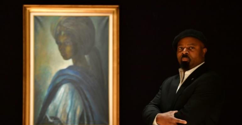 Nigerian author Ben Okri poses with a work of art by Nigerian painter and sculptor Ben Enwonwu entitled 'Tutu', the