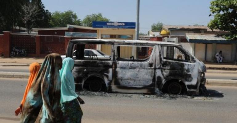 Young girls walk past a vehicle burnt on a street of Damaturu, Yobe State, northeastern Nigeria.  By Pius Utomi Ekpei (AFP/File)