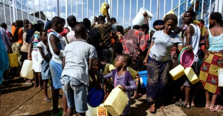 People queue for water in the Bwiza neighborhood, near central Bujumbura in 2015.  By Jennifer Huxta (AFP/File)