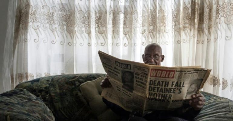 Phillip Mabelane, paging through a newspaper from the period, has been battling for 40 years for an investigation into the truth behind his son's 1977 death under apartheid.  By TADEU ANDRE (AFP)