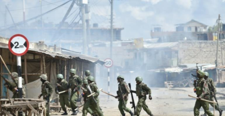 Police charge in an alley during demonstrations in a Nairobi suburb, in November 2017.  By TONY KARUMBA (AFP/File)