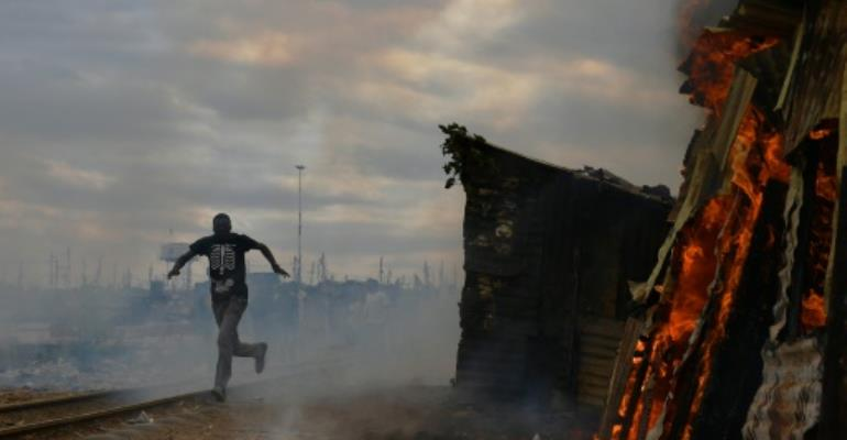 Protestors burnt a shack to the ground in a Nairobi slum as violent demonstrations against Kenya's presidential election results flared for a second day.  By CARL DE SOUZA (AFP)