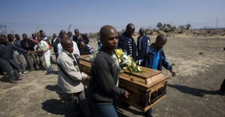A group of men in August 2012 carry the coffin of one of the striking miners killed by police.  By Rodger Bosch (AFP/File)