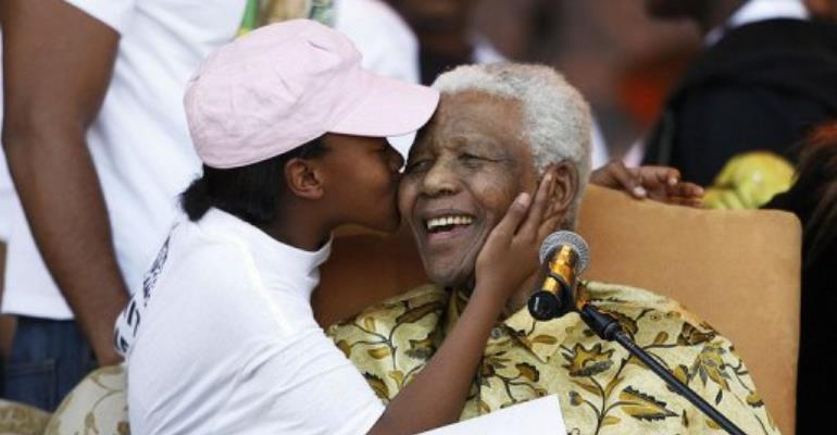 Nelson Mandela receives a kiss from one of his grandchildren in 2008. He is to spend his 94th birthday with his family.  By Gianluigi Guercia (AFP/File)