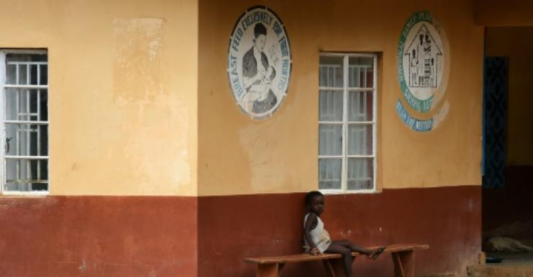 A child under quarantine sits outside a health center in Lokomasama, the biggest chiefdom in Sierra Leone's Port Loko province, on November 8, 2014.  By Francisco Leong (AFP/File)