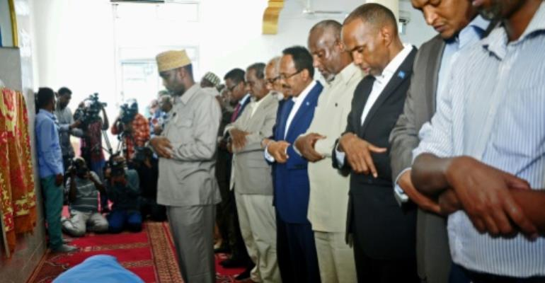 Somali President Mohamed Abdullahi Farmajo (centre) prays over the body of Abbas Abdullahi Siraji, who was assassinated in May 2017.  By Mohamed Abdiwahab (AFP/File)