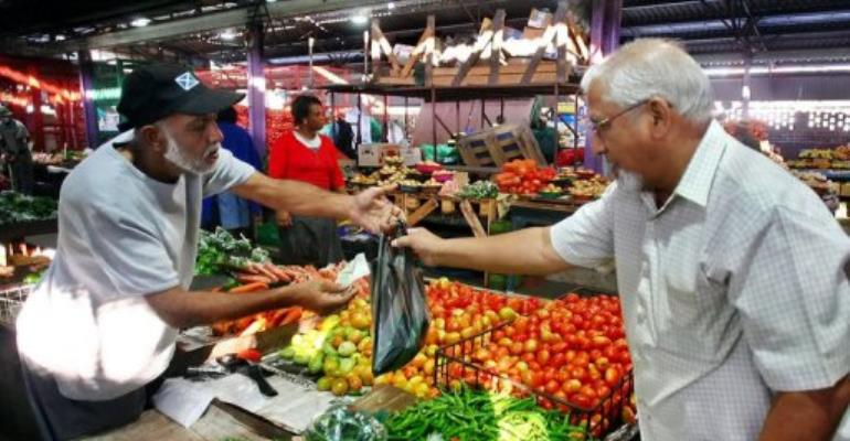 A customer pays a vendor at a market in Durban on May 22, 2010.  By Rajesh Jantilal (AFP/File)