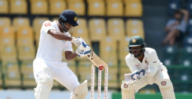Sri Lanka batsman Dimuth Karunaratne plays a shot as Zimbabwe wicketkeeper Regis Chakabva looks on during the fourth day of the one-off Test match at the R Premadasa Cricket Stadium in Colombo on July 17, 2017.  By ISHARA S. KODIKARA (AFP)