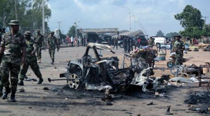 Military officers walk past the remains of a car after an explosion on July 23, 2014 in Kaduna, Nigeria.  By Victor Ulasi (AFP)
