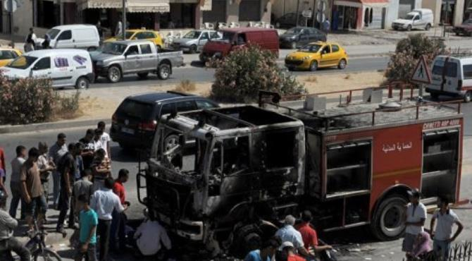 People look a charred truck in Essijoumi.  By Fethi Belaid (AFP)