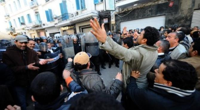 Demonstrators clash with Tunisian security force members in December 2010 in Tunis.  By Fethi Belaid (AFP/File)