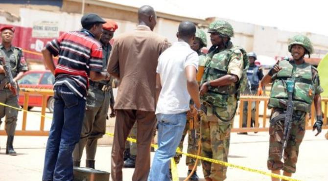 Soldiers speak with people wanting to cross the cordonned-off roads in Abuja.  By Pius Utomi Ekpei (AFP/File)