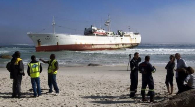 Members of salvage diving crews and media stand on the beach near the stranded fishing trawler.  By Rodger Bosch (AFP)