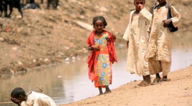 Sudanese children stand next to a water canal in the eastern Kassala State.  By Ashraf Shazly (AFP/File)