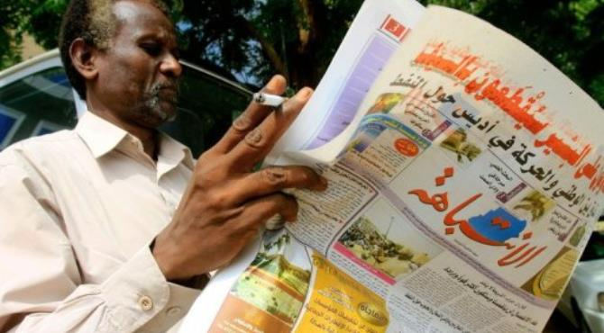 A Sudanese man reads a newspaper as he smokes a cigarette in the capital Khartoum.  By Ashraf Shazly (AFP)
