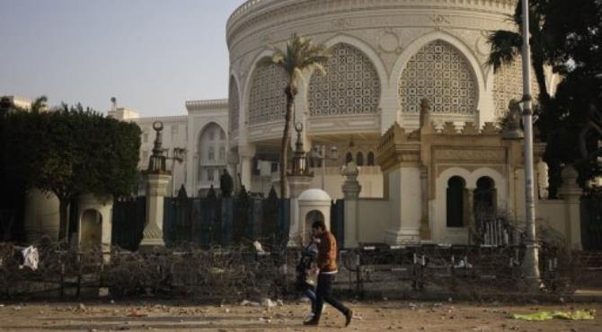 An Egyptian couple walks past a damaged barbed wire fence outside the presidential palace in Cairo on February 2, 2013.  By Gianluigi Guercia (AFP)