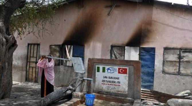 File photo taken on May 11, 2014 shows a young girl fetching water outside a house burnt by suspected Boko Haram insurgents in Gamboru Ngala district, Borno State in northeastern Nigeria.  By  (AFP/File)