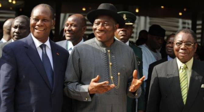 Outgoing chairman Nigerian President Goodluck Jonathan (C) passes the torch to Ivorian President Alassane Ouattara (L).  By Pius Utomi Ekpei (AFP)