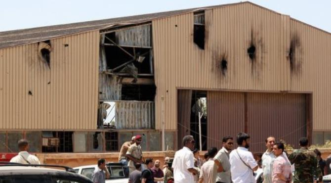 Libyans gather outside a damaged warehouse in the al-Rahaba area following deadly overnight clashes.  By Abdullah Doma (AFP)