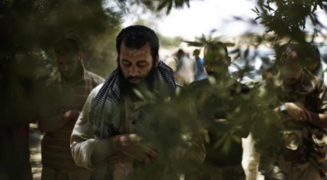 Rebel fighters pray as they await the order to enter the southwest Libyan village of Gazaia.  By Alessio Romenzi (AFP)