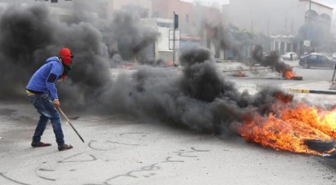 A Libyan protester stands next burning tyres as residents block a street in the capital Tripoli on March 2, 2014.  By Mahmud Turkia (AFP)