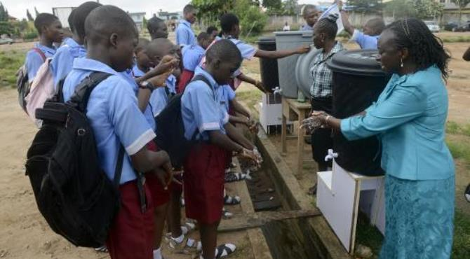 A teacher demonstrates washing procedures to pupils prevent the spread of the Ebola virus at a school in Lagos on October 8, 2014.  By Pius Utomi Ekpei (AFP/File)