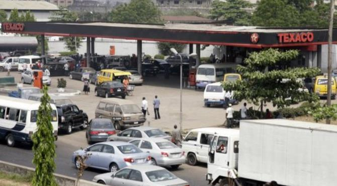Motorists queue to buy fuel at a filling station in Lagos.  By Pius Utomi Ekpei (AFP/File)