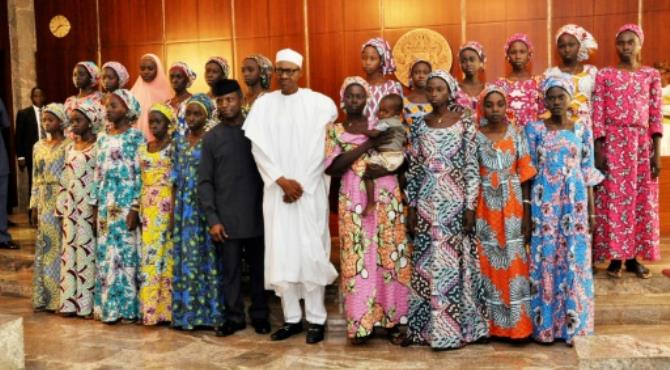 Nigerian President Muhammadu Buhari (C) poses at State House in Abuja on October 19, 2016 with the 21 Chibok girls who were released by Boko Haram the previous week.  By Philip OJISUA (AFP/File)