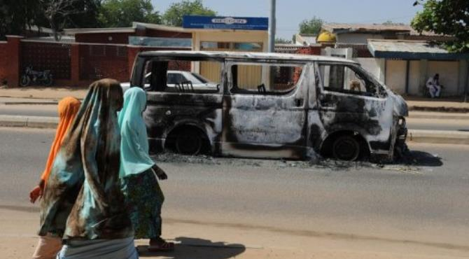 Young girls walk past a vehicle burnt on a street of Damaturu, Yobe State, northeastern Nigeria.  By Pius Utomi Ekpei (AFP/File)